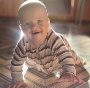 Ein Baby lacht in die Kamera.